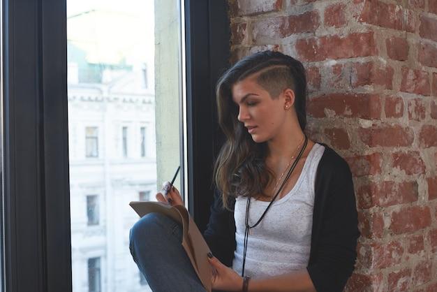 Porträt des modischen jungen gemischten hipster-mädchens mit rasiertem seitenhaarschnitt, das auf fensterbank sitzt, sich auf rote backsteinmauer stützt, notizen in ihrem tagebuch macht, inspirierten blick. menschen und lebensstil