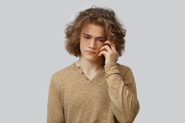 Porträt des modischen jungen männlichen hipsters mit voluminösem welligem haar, das gesicht berührt und mit ernsthaft besorgtem ausdruck nach unten schaut und über einige probleme nachdenkt. nachdenklicher typ posiert