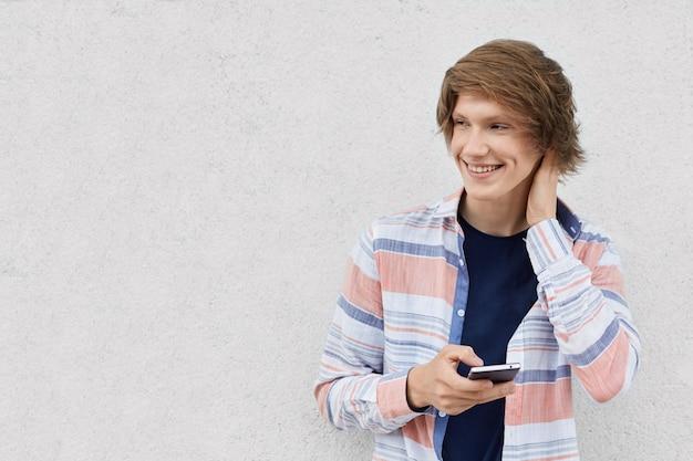 Porträt des modischen kerls mit stilvoller frisur, die hemd hält, das smartphone-nachrichten online hält oder soziale netzwerke surft