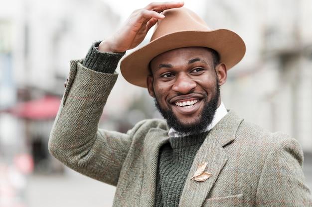 Porträt des modischen mannes, der draußen lächelt
