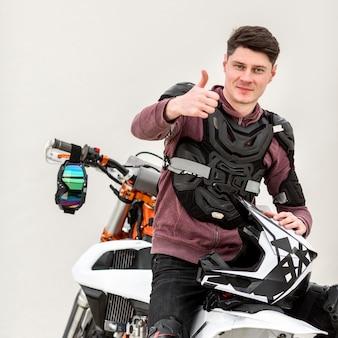 Porträt des motorradfahrers, der daumen oben zeigt