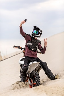 Porträt des motorradfahrers, der ein selfie in der wüste nimmt