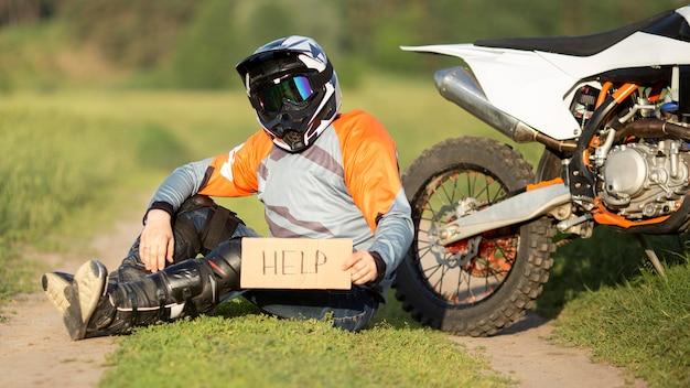 Porträt des motorradfahrers, der hilfeschilder hält