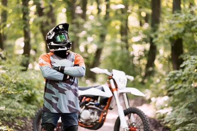 Porträt des motorradfahrers, der im wald aufwirft