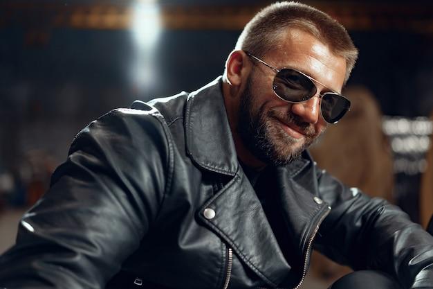Porträt des motorradfahrers des bärtigen mannes in der dunklen sonnenbrille auf dunklem gebäude