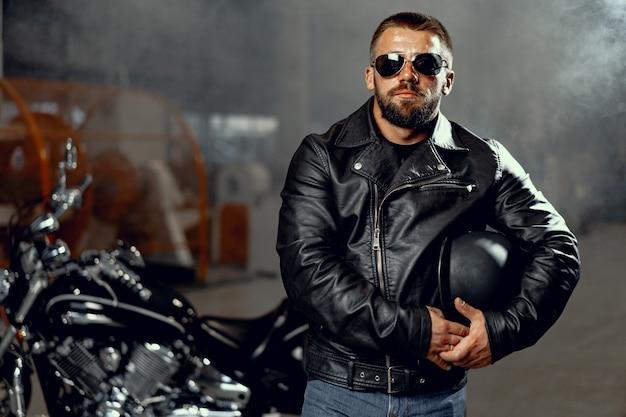 Porträt des motorradfahrers des bärtigen mannes in der dunklen sonnenbrille auf dunklem hintergrund