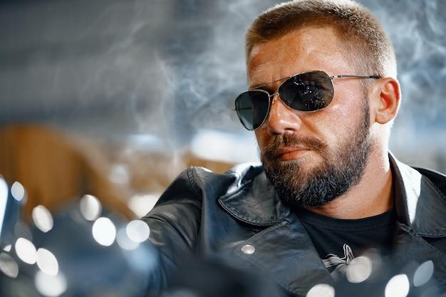 Porträt des motorradfahrers im schwarzen lederoutfit