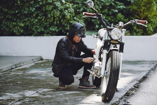 Porträt des motorradfahrers sein fahrzeug für eine fahrt vorbereitend