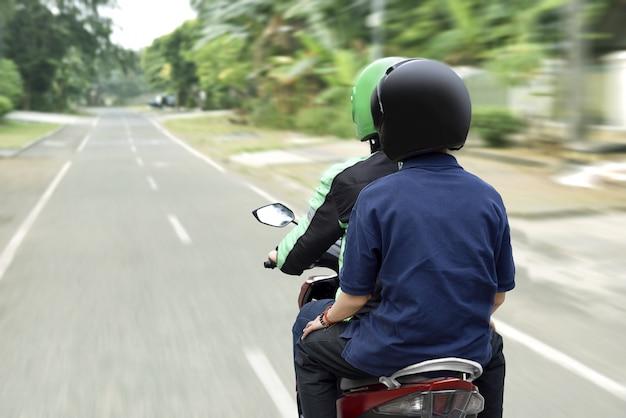 Porträt des motorradtaxifahrers den passagier zu seinem bestimmungsort liefernd