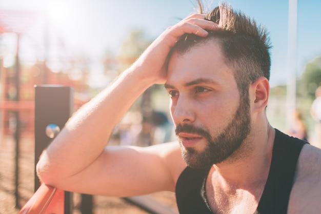 Porträt des müden fitness-kerls am heißen sonnigen tag. sportler, der sich nach einem harten training ausruht.