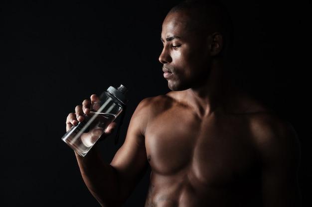 Porträt des müden jungen afroamerikanischen sportmannes, der flasche wasser hält