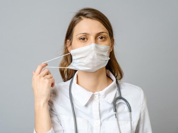 Porträt des müden jungen arztes, der medizinische gesichtsmaske abhebt