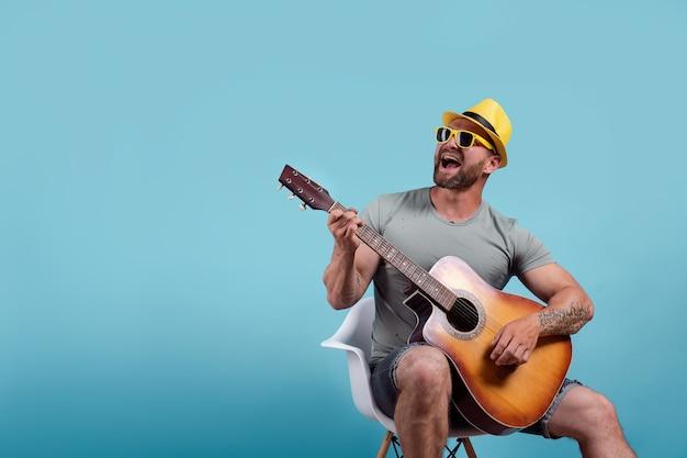 Porträt des musikers, der akustikgitarre spielt und singt
