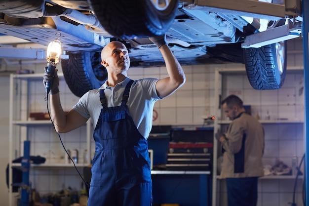 Porträt des muskelmechanikers, der unter auto auf aufzug steht, während fahrzeug in autoreparaturwerkstatt inspiziert, raum kopiert