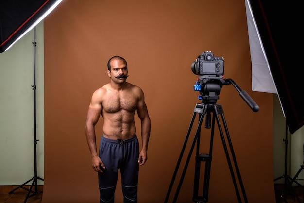 Porträt des muskulösen indischen mannes mit schnurrbart hemdlos vlogging mit kamera