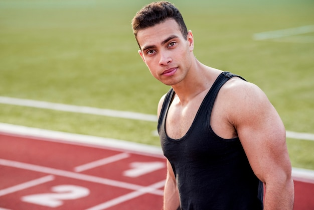 Porträt des muskulösen jungen mannes auf rennstrecke