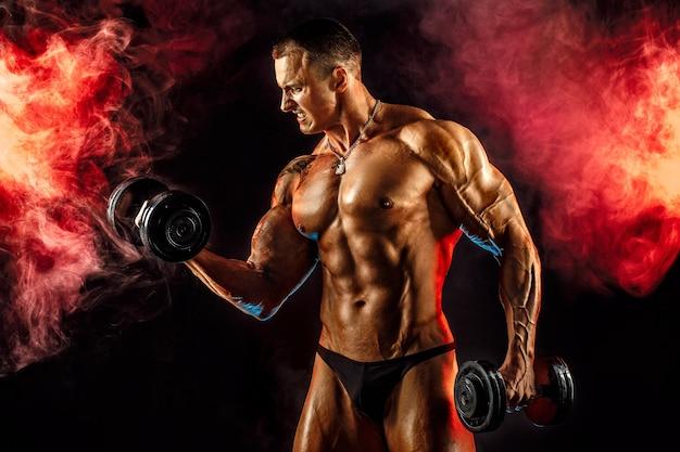 Porträt des muskulösen mannes, der hantel im roten rauch anhebt. studioaufnahme.