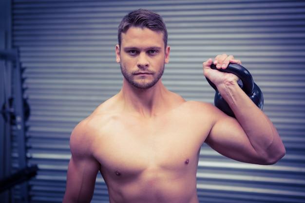 Porträt des muskulösen mannes eine kettlebell anhebend