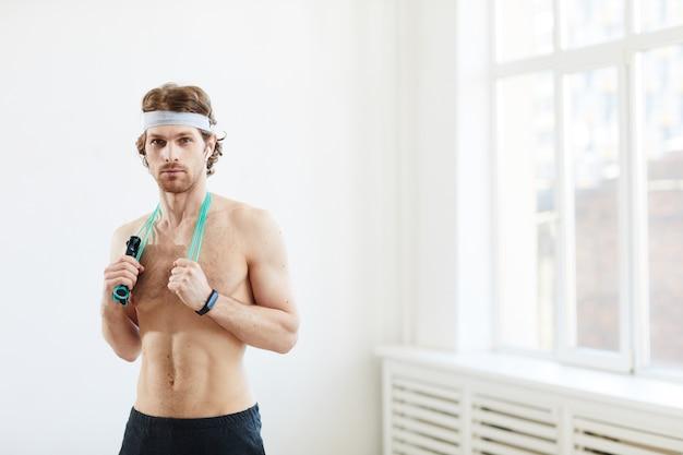 Porträt des muskulösen mannes mit springseil um seinen hals, der kamera nach sporttraining betrachtet