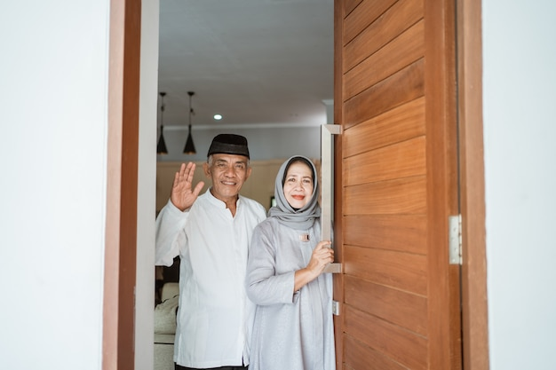 Porträt des muslimischen asiatischen älteren paares, das an der haustür steht und darauf wartet, dass die familie kommt