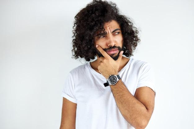 Porträt des nachdenklichen jungen arabischen arabischen mannes lokalisiert im studio, lockiger dunkelhaariger mann