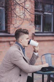 Porträt des nachdenklichen jungen geschäftsmannes, der kaffee vom pappbecher trinkt
