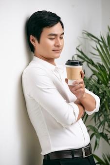 Porträt des nachdenklichen jungen vietnamesischen geschäftsmannes mit tasse herausgenommenem kaffee, der an wand lehnt