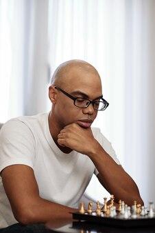 Porträt des nachdenklichen kahlen schwarzen mannes, der über die nächste bewegung im schachspiel nachdenkt