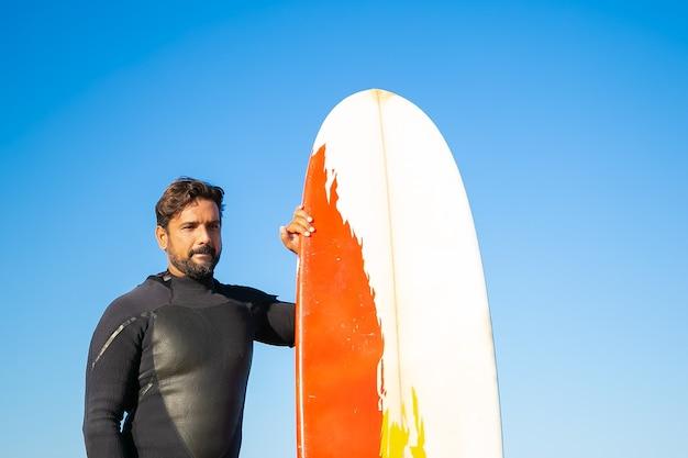 Porträt des nachdenklichen männlichen surfers, der mit brett steht. kaukasischer brünetter mann, der neoprenanzug trägt, surfbrett hält und sich freut