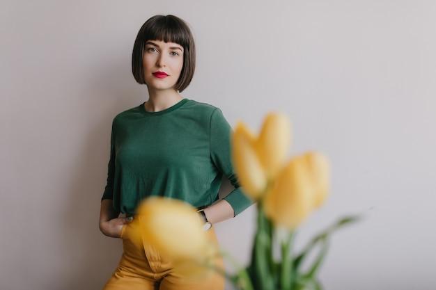Porträt des nachdenklichen stilvollen mädchens im grünen pullover. innenfoto der erstaunlichen brünetten frau, die nahe gelben blumen aufwirft.