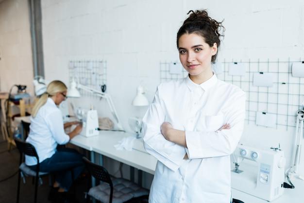 Porträt des nähmaschinenbedieners in der langen weißen bluse, die arme auf brust gegen arbeitsplatz kreuzt