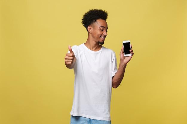 Porträt des netten afroamerikanermannes, der auf mobiltelefon mit den daumen herauf handzeichen spricht