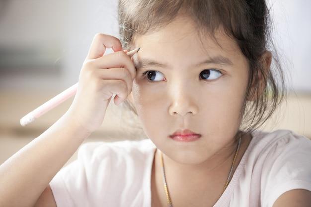 Porträt des netten asiatischen kindermädchens, das spaß denkt und hat, im raum zu zeichnen und zu malen