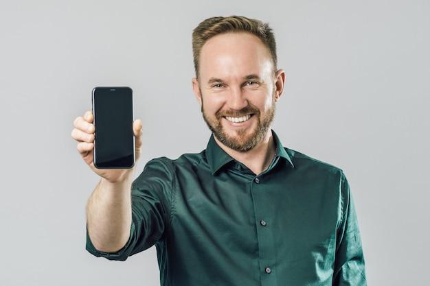 Porträt des netten attraktiven mannes, der smartphone zeigt