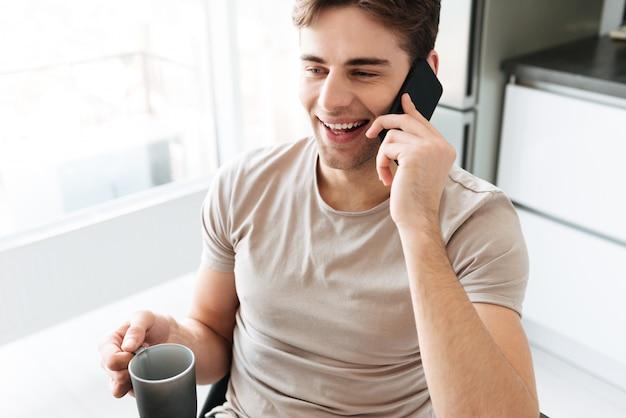 Porträt des netten attraktiven mannes, der zu hause am telefon spricht