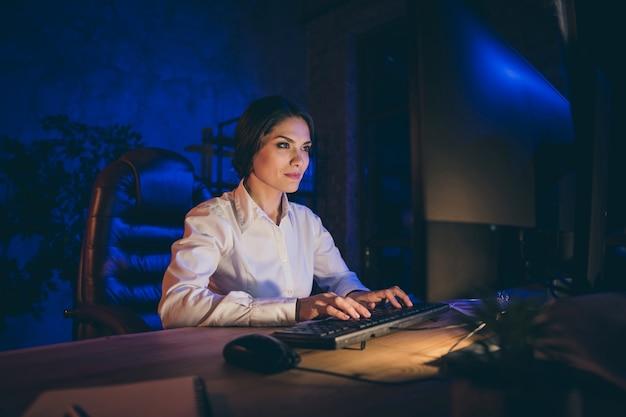 Porträt des netten attraktiven reizenden schicken schicken stilvollen inhalts dame finanzier-ökonom-agent-makler-firmeninhaber-vermarkter, der an disctance arbeitet, das berichtsfrist bei nacht dunkler arbeitsplatzstation vorbereitet