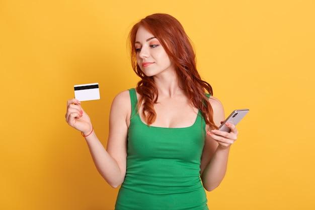 Porträt des netten attraktiven rothaarigen mädchens, das in den händen bankkarte und handy hält