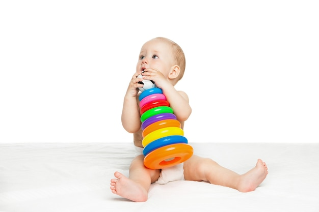 Porträt des netten babys, das mit buntem spielzeug auf weißem hintergrund sitzt und spielt