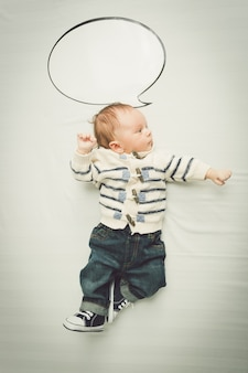 Porträt des netten babys, das mit leerer sprechblase aufwirft