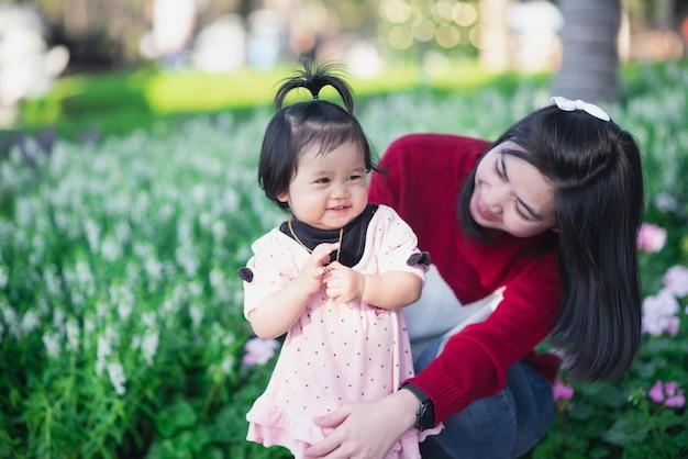 Porträt des netten babys und ihrer mutter reisen am blumengarten