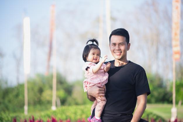Porträt des netten babys und ihres vatis reisen am blumengarten