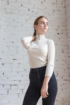 Porträt des netten durchdachten jugendlich modells, das weiße strickjacke und schwarze jeans trägt. kaukasische dünne junge frau mit blonden haaren steht vor weißer mauer. natürliche hübsche dame, die im studio steht
