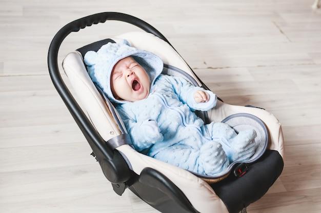 Porträt des netten gähnenden mischrennenbabys, das im autositz sitzt. sicherheit beim kindertransport.