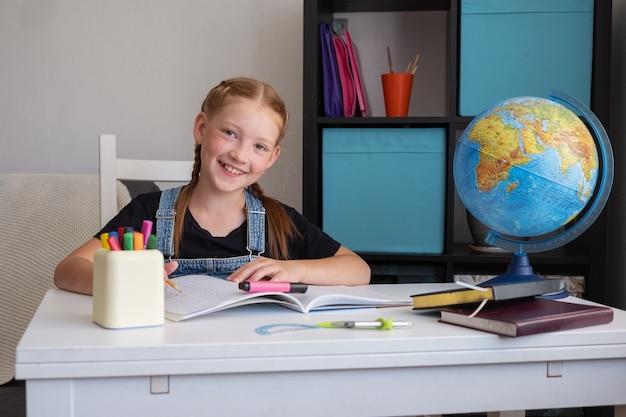 Porträt des netten glücklichen kaukasischen rothaarigenmädchens, das zu hause studiert, fernbildungskonzept. hausaufgaben schreiben. quarantäne. globus auf dem tisch. zurück zum schulkonzept.