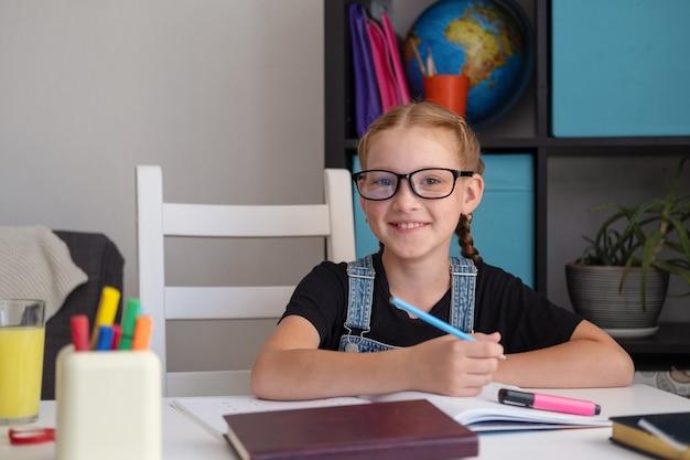 Porträt des netten glücklichen kaukasischen rothaarigenmädchens in den brillen, die zu hause studieren, fernbildungskonzept. hausaufgaben schreiben. quarantäne. zurück zum schulkonzept.