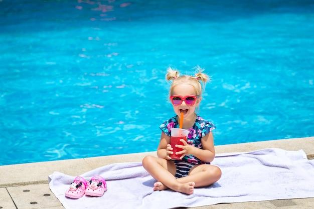 Porträt des netten glücklichen kleinen mädchens, das spaß im swimmingpool hat und frischen wassermelonensaft trinkt