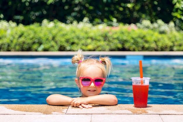 Porträt des netten glücklichen kleinen mädchens, das spaß im swimmingpool hat