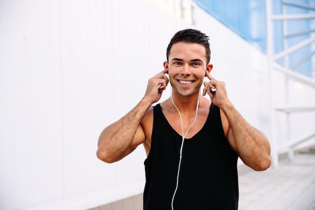 Porträt des netten hübschen muskulösen kerls, der musik im kopfhörer hört