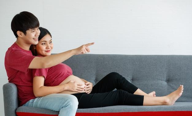 Porträt des netten jungen asiatischen paares, der zu hause zusammen auf einer couch sitzt. ein mann lächelt und zeigt etwas nach vorne, während sich eine schwangere frau glücklich an seine brust lehnt.