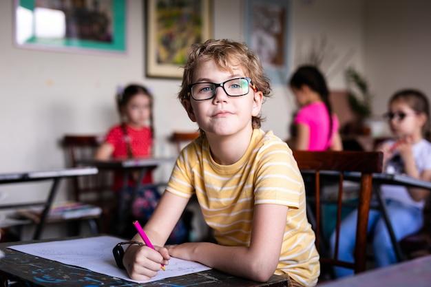 Porträt des netten jungen mit skizzenstift und -papier am schreibtisch im klassenzimmer.